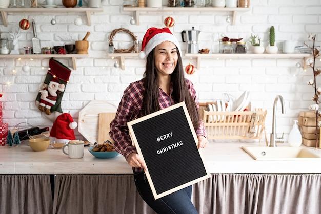 メリークリスマスという言葉で黒い文字板とサンタの帽子の美しいラテン女性