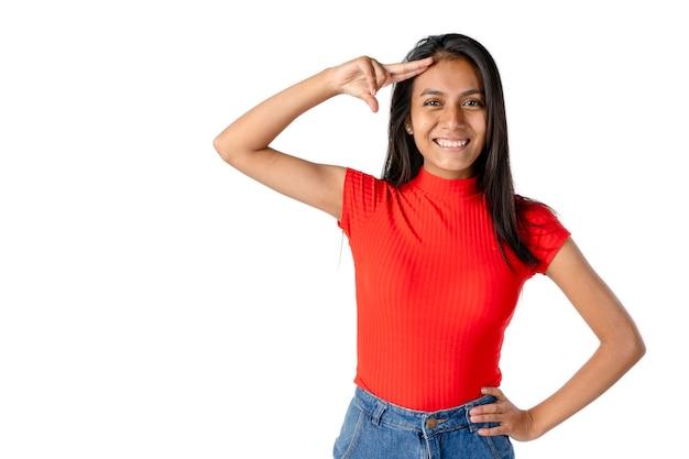 아름다운 라틴 여성은 이마에 손을 얹고 순수한 흰색 배경에 행복한 태도로 손을 흔들고 있습니다.