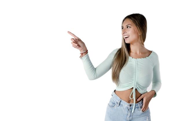 아름다운 라틴 여성은 빈 공간을 가리키며 순수한 흰색 배경에서 웃고 있는 쪽을 바라보고 있습니다. 스튜디오에서 가져 가라.