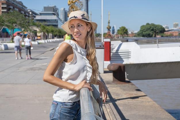 Красивая латинская женщина стоит и опирается на перила моста в солнечный день