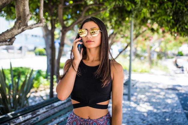 Красивая латинская женщина разговаривает по телефону и улыбается в парке
