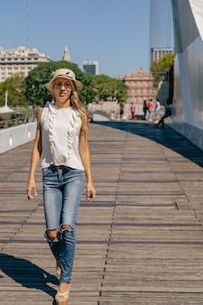Красивая латинская женщина идет по мосту с деревянным полом. концепция женский стиль.