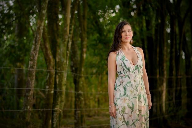 森の真ん中で身に着け、モデリングし、笑顔の美しいラテン女性。