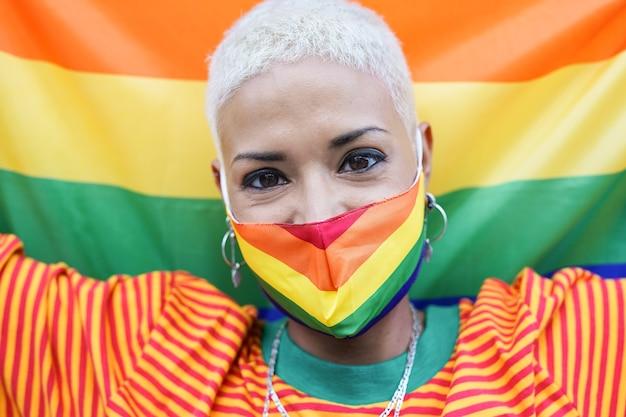 保護フェイスマスクを身に着けている美しいラテン女性-lgbtレインボーフラッグ