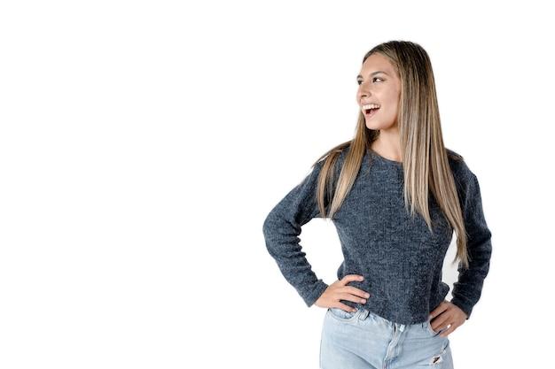 팔짱을 낀 아름다운 라틴 여성이 순백의 배경을 가진 옆으로 웃고 있는 모습을 옆으로 가로질러 서 있습니다. 스튜디오에서 가져 가라.