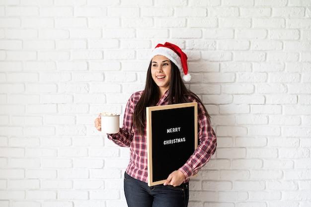 メリークリスマスという言葉で黒い文字板を持つ美しいラテン女性