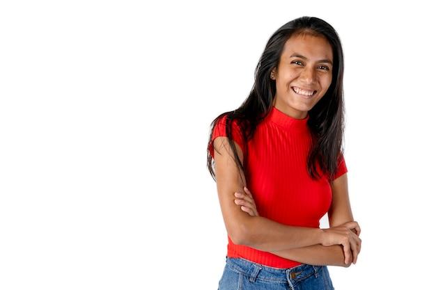 팔짱을 끼고 순수한 흰색 배경으로 정면을 향해 웃고 있는 빨간 셔츠를 입은 아름다운 라틴 여성.
