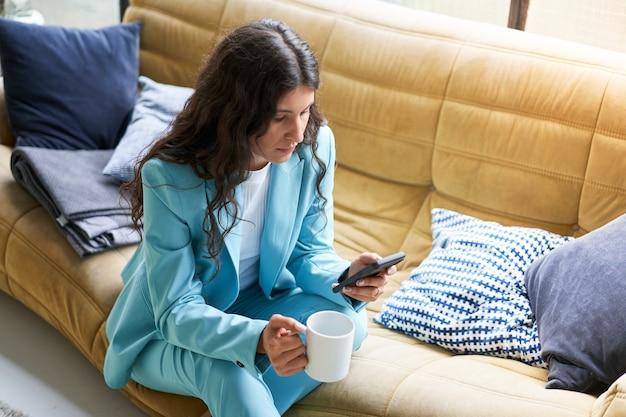 아름다운 라틴 여성 사업가가 스마트폰을 사용하는 동안 소파에 앉아 휴식 시간에 커피를 마십니다.