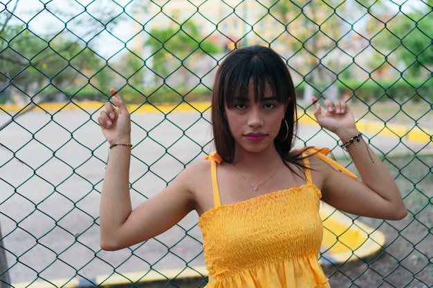 Beautiful latina in the street leaning on a wire mesh