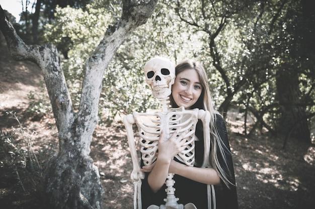 Beautiful laughing woman hugging behind skeleton