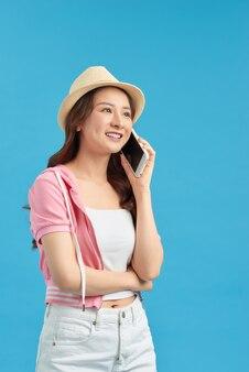 青い背景の携帯電話で話している夏の帽子の美しい笑う女性