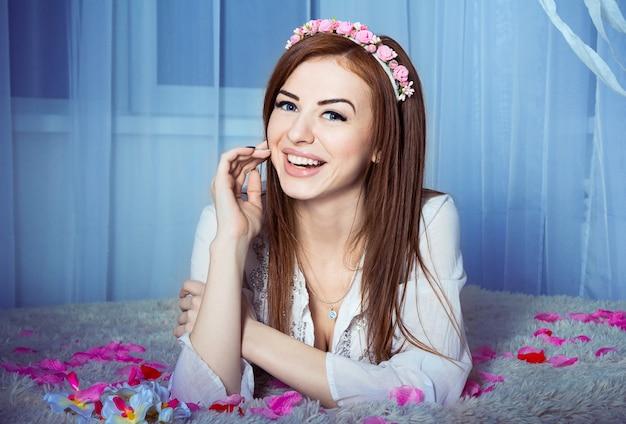Красивая смех женщина, лежа на кровати с розовыми и красными лепестками роз