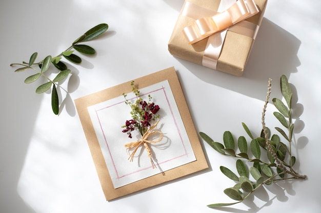 花の装飾と白い机の背景、上面図、フラットレイにカードモックアップと美しいレイアウト。結婚式の招待状または母の日の挨拶の概念
