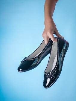 青い背景の上の子供の手に美しい革の靴。スタイリッシュでファッショナブルな革の女性の靴。