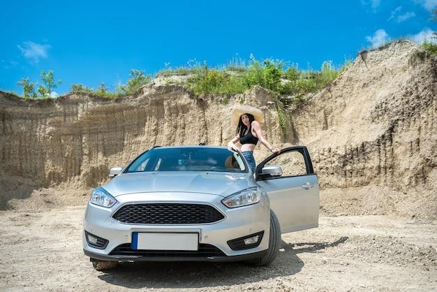 夏休みの砂浜でポーズをとる車の近くの美しい脚