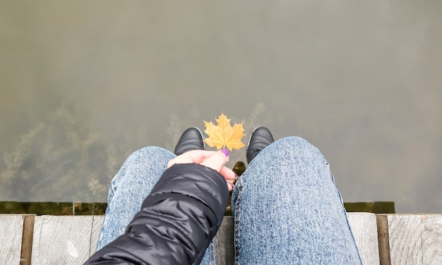 Beautiful legs of a girl in jeans are sitting on a wooden bridge by the lake, holding a yellow maple leaf in their hands. autumn warm and sunny day. view from above. autumn concept.