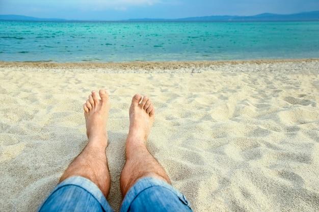 Красивые ноги на песке морского фона греции