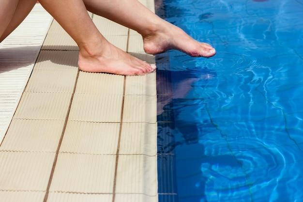 海の背景のプールの近くの女の子の美しい脚