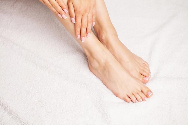 Красивые ножки женщины со свежим французским педикюром