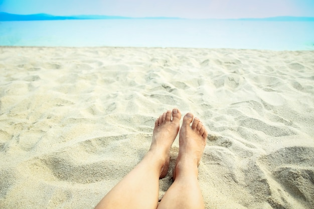 Beautiful legs in the sand of the sea greece background
