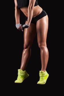 美脚。黒の背景に美しい女性の脚の側面のトリミングされた画像