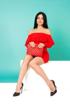 흰색 벤치에 앉아 하이힐 구두와 지갑 손 가방 빨간 드레스를 입고 아름다운 다리 여자-이미지