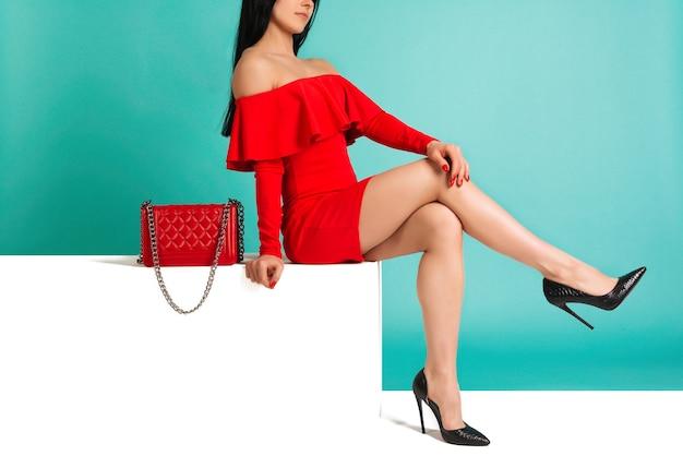白いベンチに座っているハイヒールの靴と財布のハンドバッグと赤いドレスを着ている美しい脚の女性