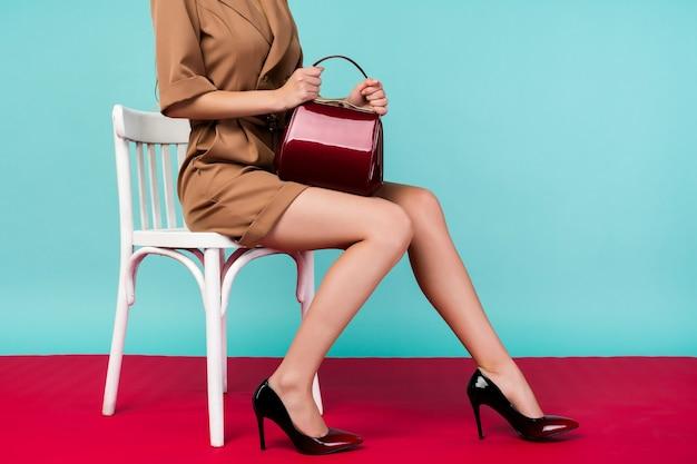 빨간 지갑 손 가방을 가진 아름 다운 다리 여자