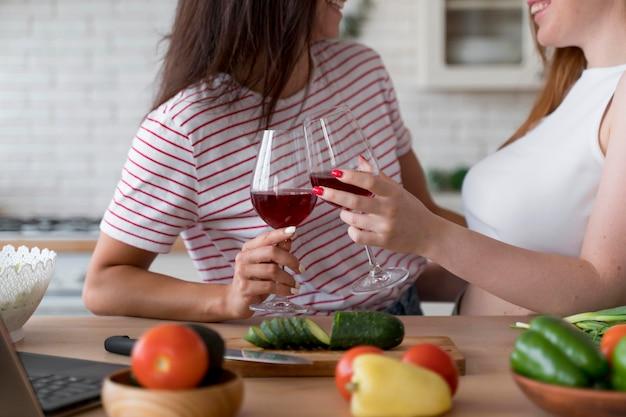 いくつかのグラスワインで応援する美しいレズビアンのカップル