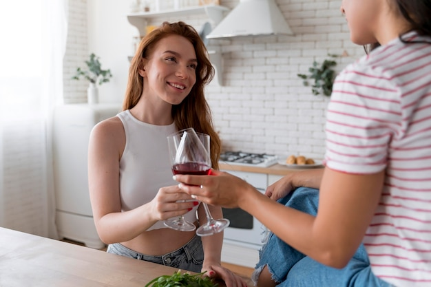 Beautiful lesbian couple cheering with some glasses of wine