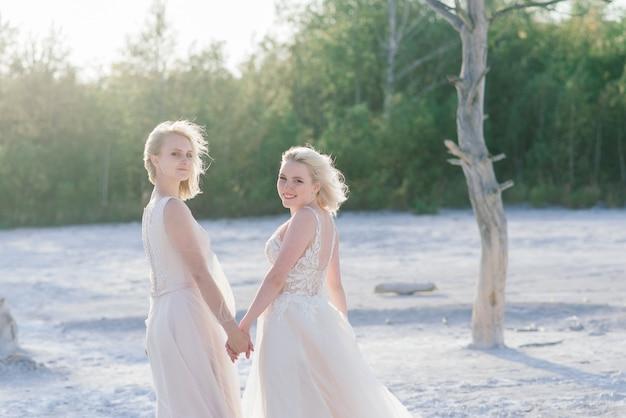 Красивая лесбийская пара гуляет по песку вдоль берега реки в день свадьбы