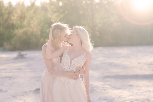 Beautiful lesbian couple walking on sand along a river bank on their wedding day