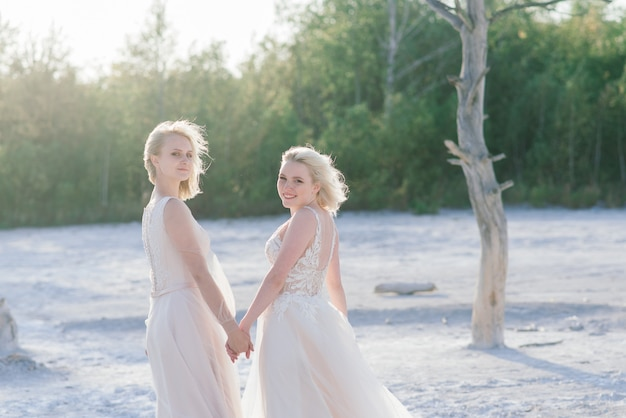Beautiful lesbian couple walking on sand along river bank on their wedding day