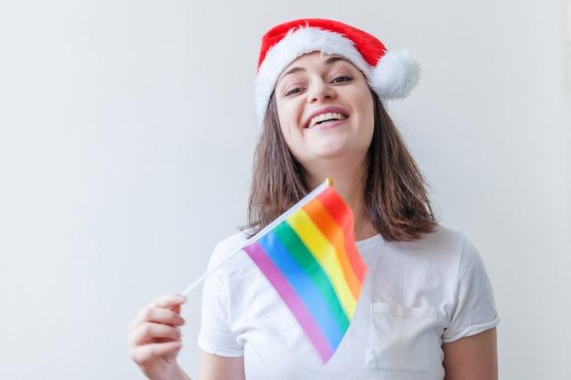 Lgbtの虹色の旗と赤いサンタクロースの帽子の美しいレズビアンの女の子