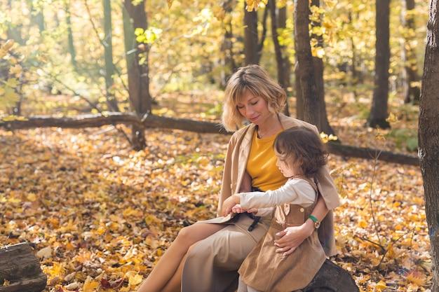 아름다운 라이프 스타일 가을 사진 엄마와 아이는 공원 따뜻한 햇빛에서 저녁 산책