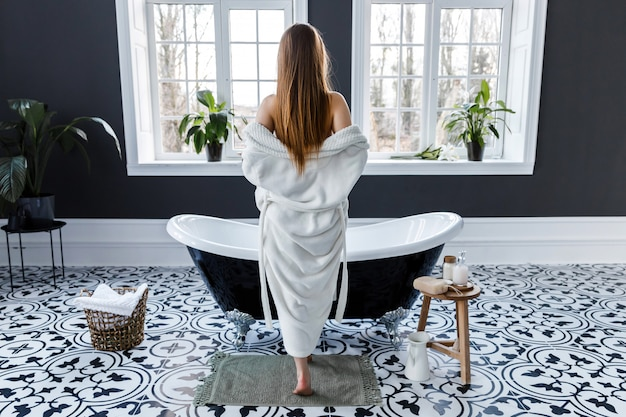 Beautiful light bathroom with large windows. young woman removes her white robe while standing at the bath