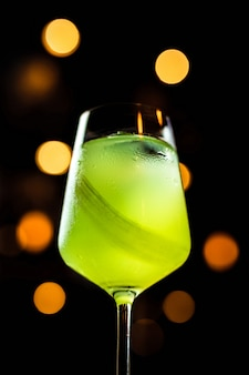 A beautiful light green cocktail with celery in a wine glass, bokeh lights, selective focus