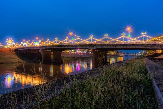 タイのピサヌロックで開催されるナレスアン大祭と赤十字の年次イベントのために、レルムの道路にある橋(ナレスアン橋)の夜のナン川の美しい光。
