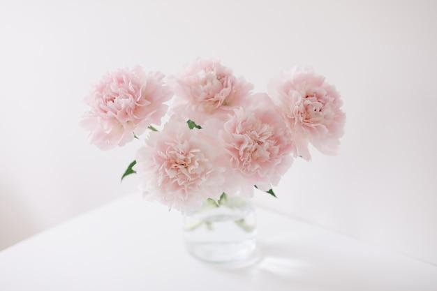 흰색 테이블과 배경에 있는 유리 꽃병에 있는 분홍색 모란의 아름다운 밝은 분홍색 신선한 자른 꽃다발