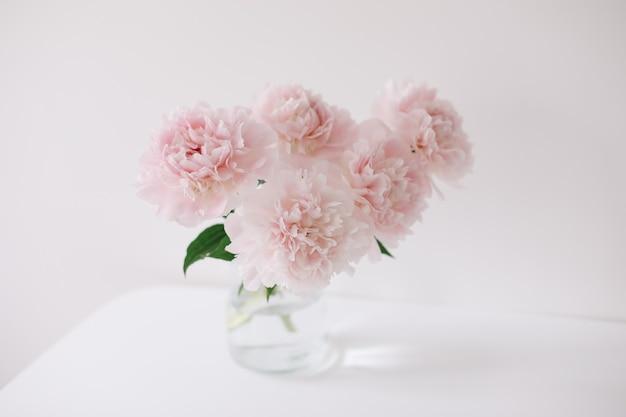 白いテーブルと背景の上のガラスの花瓶にピンクの牡丹の美しいライトピンクの新鮮なカットの花束