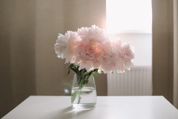 창가에 있는 흰색 테이블에 있는 유리 꽃병에 분홍색 모란의 아름다운 밝은 분홍색 신선한 자른 꽃다발