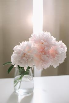 窓際の白いテーブルの上のガラスの花瓶にピンクの牡丹の美しいライトピンクの新鮮なカットの花束