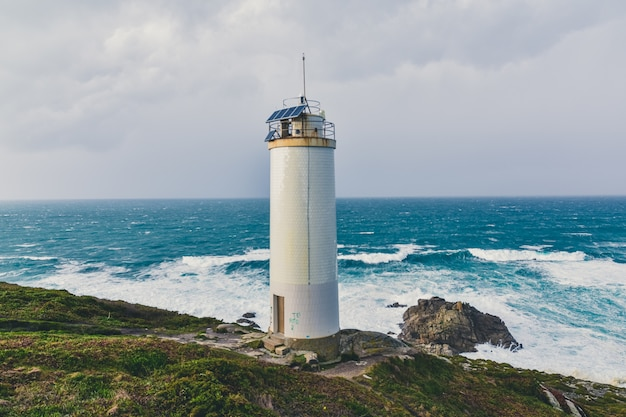 Beautiful lighthouse in the cliffs with the magnificent stormy sea