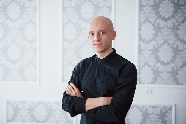 Beautiful lighting. portrait of cheerful guy in the classic black shirt with arms crossed