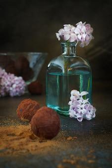 Bellissimo bouquet lilla in una bottiglia di vetro blu e deliziosi cioccolatini
