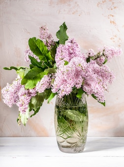 Beautiful lilac bouquet in crystal vase on light textured background