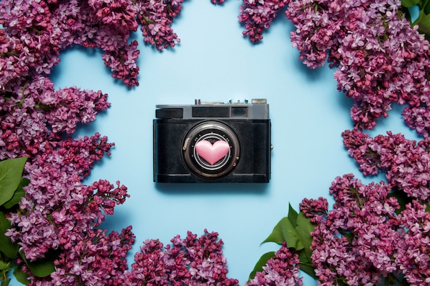 Beautiful lilac bouquet and retro photo camera on a blue background