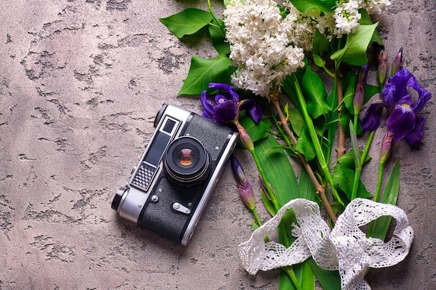 灰色のコンクリートの美しいライラックの花と古いカメラ