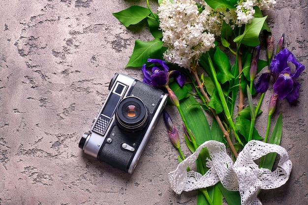 Beautiful lilac flower and old camera on gray concrete