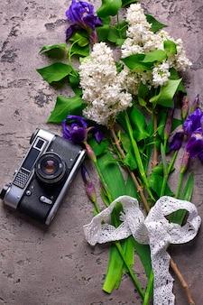 美しいライラックの花と灰色のコンクリートの背景に古いカメラ。